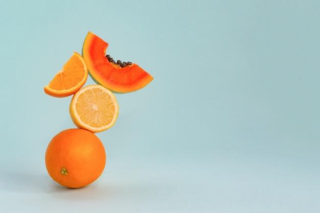 Equilíbrio de frutas frescas em uma superfície azul.
