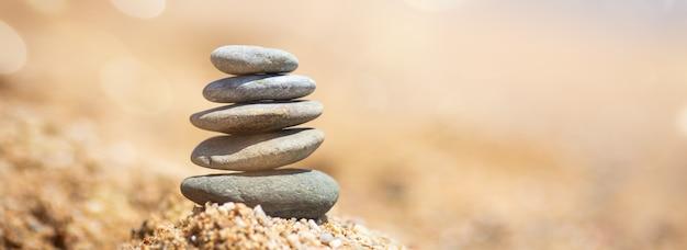 Equilíbrio de pedras na praia, dia de sol