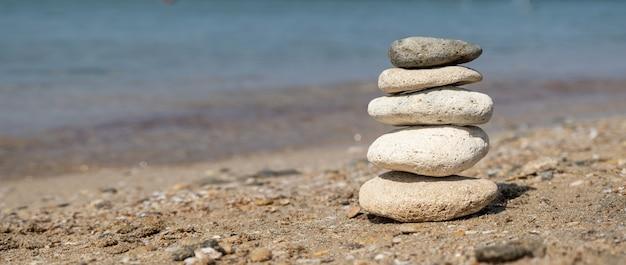 Equilíbrio de pedras na praia, dia de sol.