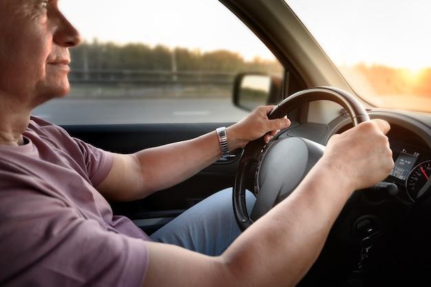Equipa as mãos no volante do carro de viagem de verão em direção ao pôr do sol