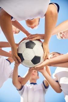 Equipa de futebol júnior segurando bola