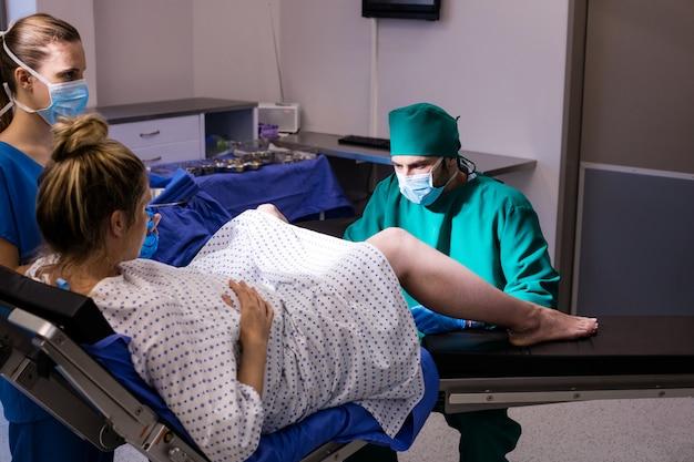 Equipa médica que examina mulher grávida durante o parto
