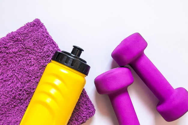 Equipamento de academia de ginástica. dumbbells com toalha e engarrafador. calçado de treino. treinadores de esporte no fundo branco. desporto, estilo de vida saudável e conceito de objetos