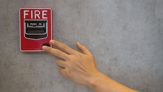 Equipamento de alarme ou alerta de emergência de incêndio ou campainha na cor vermelha com a mão no prédio por segurança.