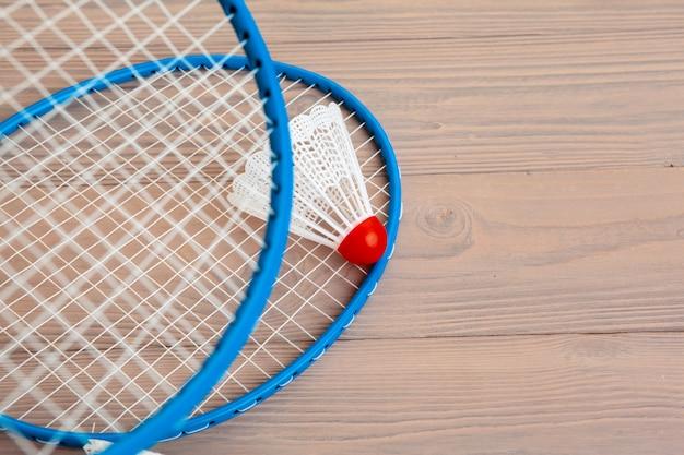 Equipamento de badminton. raquetes e peteca na mesa de madeira
