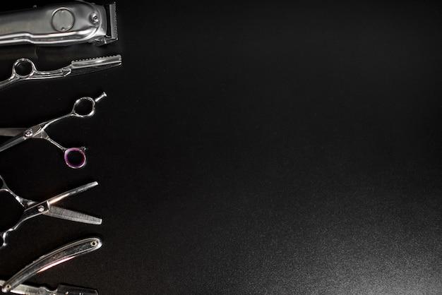 Equipamento de barbearia em fundo preto com lugar para texto. ferramentas de cabeleireiro profissional. pente, tesoura, tesoura e aparador de pêlos isolados