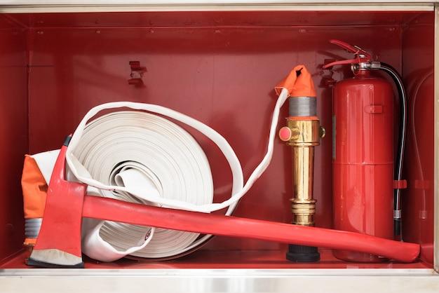 Equipamento de bombeiro de resgate, extintor, machado e linha de fogo na caixa vermelha