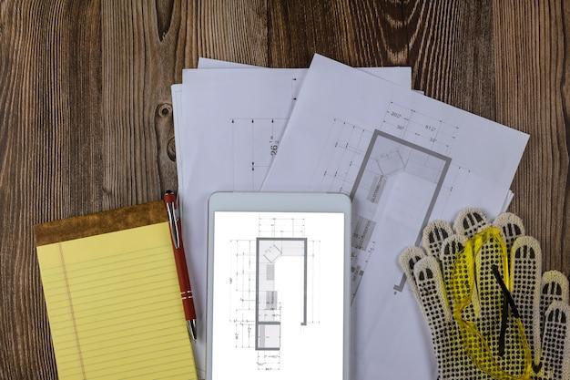 Equipamento de canteiro de obras engenheiro de papel entre plano de planta de gabinete de cozinha de espaço de trabalho no tablet digital