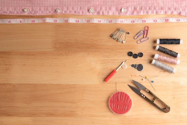 Equipamento de costura colocado em madeira áspera