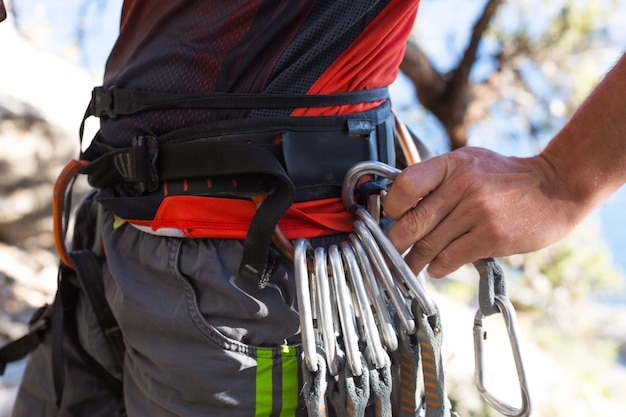Equipamento de escalada em um alpinista masculino: sapatas de rocha, corda, tração rápida, dispositivo de segurança, arnês. turismo esportivo de montanha, estilo de vida ativo, esportes radicais