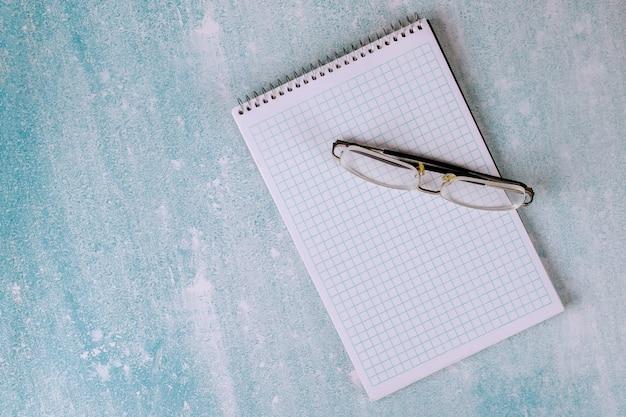 Equipamento de escritório no local de trabalho em um caderno em branco aberto em óculos