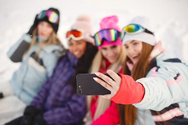 Equipamento de esqui nas mãos de meninas. momentos felizes juntos. as meninas aprendem a esquiar.