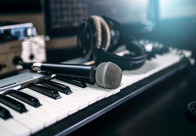 Equipamento de estúdio de música profissional, closeup. teclado musical, microfone e fones de ouvido.
