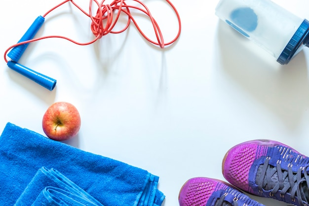 Equipamento de ginástica plano, como tênis para pular corda e toalha com maçã e pernas humanas b