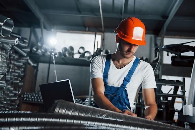 Equipamento de iluminação atrás. homem de uniforme trabalha na produção. tecnologia industrial moderna.