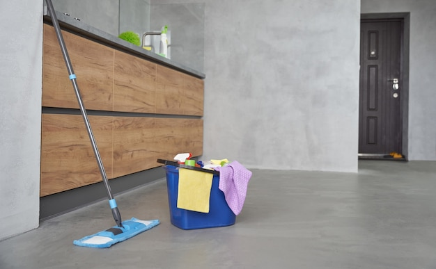 Equipamento de limpeza em casa. esfregona e balde de plástico com trapos, detergentes e diversos produtos de limpeza no chão da cozinha moderna. serviço de limpeza, trabalho doméstico, serviço de limpeza