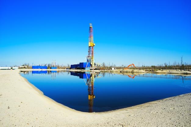 Equipamento de perfuração com reflexo na água. sibéria.