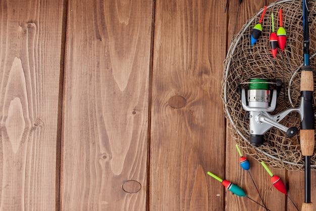 Equipamento de pesca - bóia de pesca com vara de pescar e iscas em fundo de madeira azul bonito, copie o espaço.