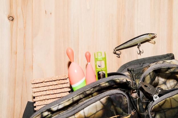 Equipamento de pesca dentro do saco de camuflagem com isca de pesca na superfície de madeira