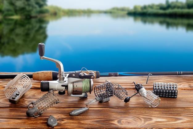 Equipamento de pesca e acessórios em cima da mesa contra o rio.