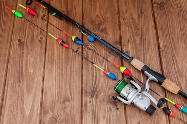 Equipamento de pesca - flutuador de pesca com vara de pescar e iscas em um lindo espaço de madeira azul, copie o espaço