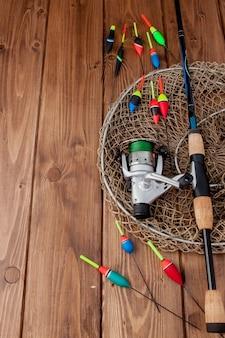 Equipamento de pesca - flutuador de pesca com vara de pescar e iscas em uma bela madeira azul