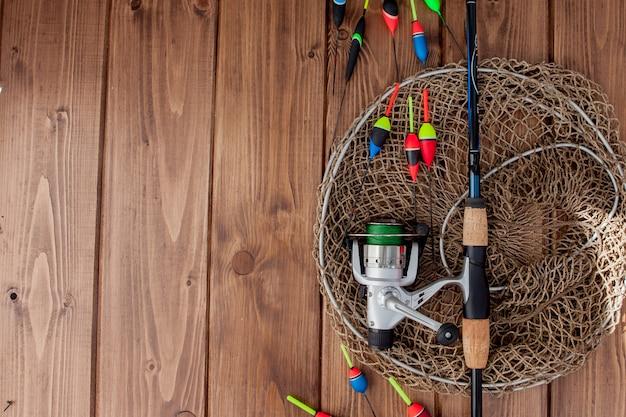 Equipamento de pesca flutuador de pesca com vara de pescar e iscas na bela madeira azul
