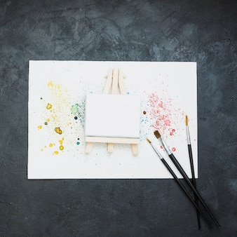 Equipamento de pintura e papel de pintura manchada sobre a superfície preta