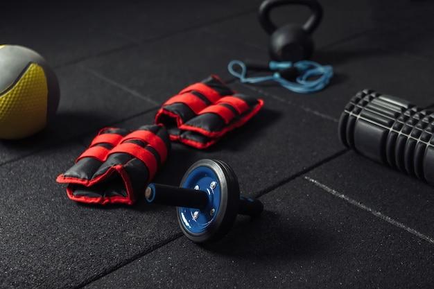 Equipamento de treinamento funcional. kettlebell e pular corda, rolo ab, medicine ball, rolo de massagem, pesos em um piso preto escuro. culturismo e fitness