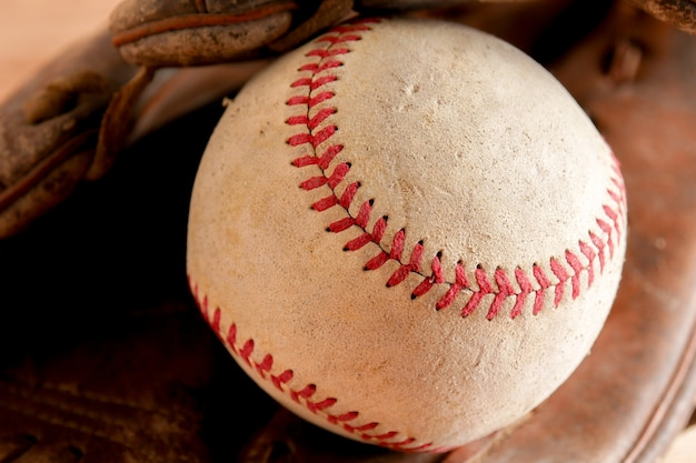 Equipamento desportivo basebol velho no fundo de madeira