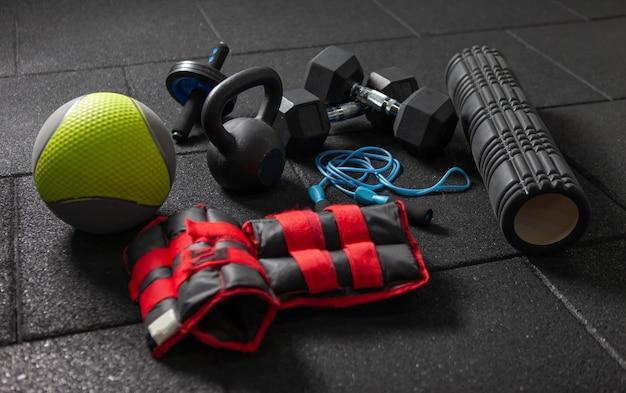 Equipamento desportivo de treino funcional. kettlebell e corda de pular, halteres, medicine ball, rolo de massagem, pesos em um chão preto escuro. culturismo e fitness