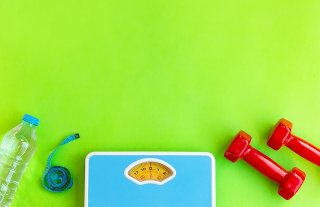 Equipamento desportivo e de treino na vista superior de fundo verde com água, medição de tipe, halteres, balanças de chão, perda de peso e conceito de atividade física, espaço de cópia de maquete