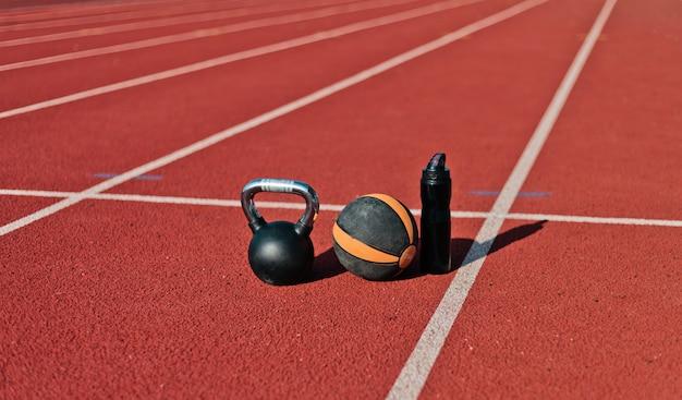 Equipamento desportivo no estádio de pista revestida de vermelho em um dia ensolarado. kettlebell, bola medicinal, garrafa de água.