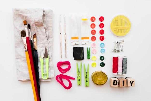 Equipamento diy; pincel; prendedor de roupa; agulha; pinos de segurança; tubo de tinta acrílica; botões; blocos diy e fita métrica isolada no pano de fundo branco