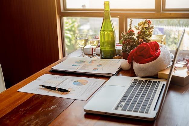 Equipamento do natal com o chapéu de santa na tabela do escritório no último dia de trabalho.