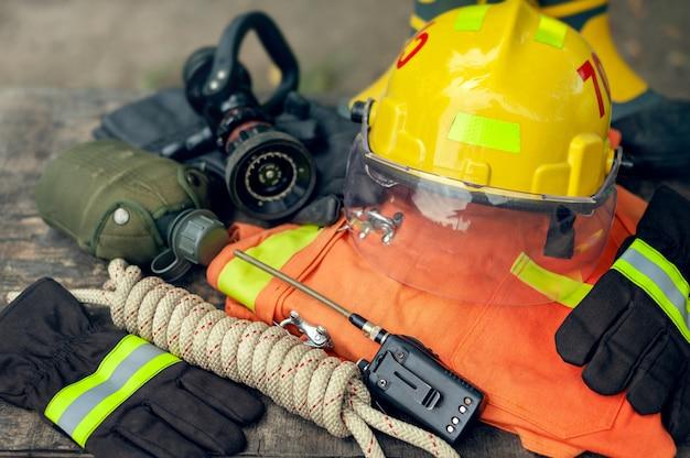 Equipamento do sapador-bombeiro no fundo velho da tabela, conceito do equipamento do fogo.