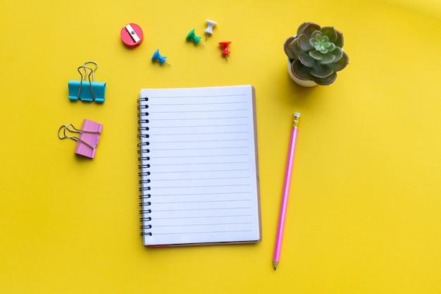 Equipamento e caderno vazio com amarelo