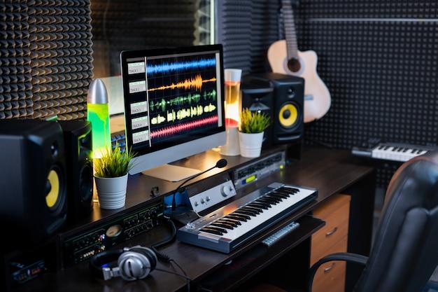 Equipamento elétrico para gravação de música e monitor de computador com faixas de mixagem de som no local de trabalho do dj ou músico moderno em estúdio