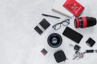 Equipamento fotográfico, caderno espiral e acessórios pessoais no fundo