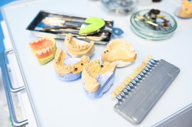 Equipamento, instrumentos e ferramentas dentais profissionais diferentes em uma clínica do escritório do stomatology dos dentistas em um fundo branco. molde de silicone da mandíbula.