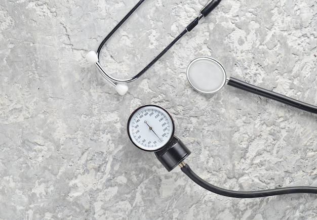 Equipamento médico cardiológico para medir a pressão em uma superfície de concreto. estetoscópio e medidor de medida. vista do topo.