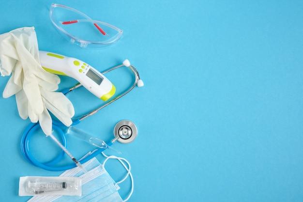 Equipamento médico em fundo azul lugar cópia vista superior estetoscópio termômetro sem contato máscara facial seringa óculos e luvas de segurança