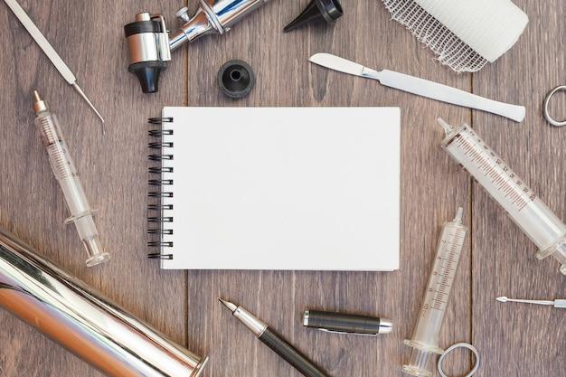 Equipamento médico está rodeado em torno do bloco de notas espiral em branco na mesa de madeira