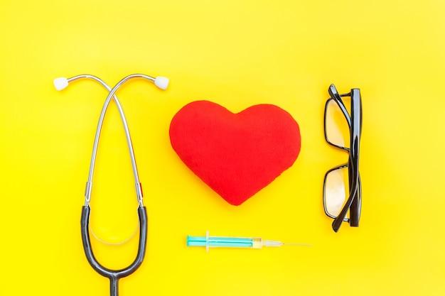 Equipamento médico estetoscópio óculos seringa coração vermelho isolado na mesa amarela