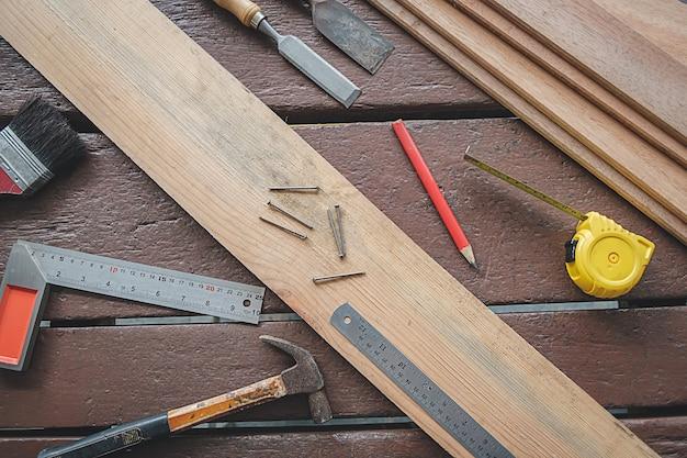 Equipamento na mesa de madeira com o homem que trabalha no fundo da oficina.
