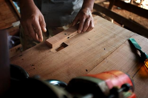 Equipamento na mesa de madeira com o homem que trabalha no fundo da oficina