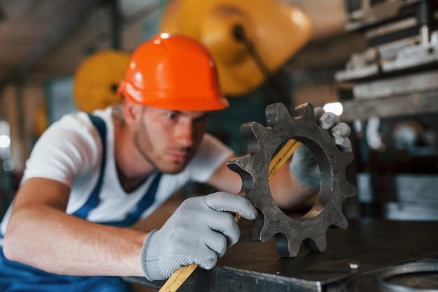 Equipamento novo. homem de uniforme trabalha na produção. tecnologia industrial moderna.