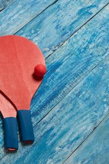 Equipamento para jogar tênis de praia na mesa de madeira azul