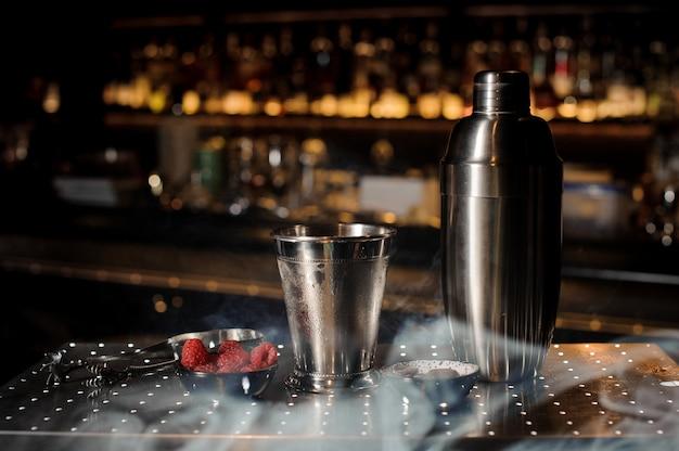 Equipamento profissional de bar, agitador, copo e tenaz dispostos no balcão do bar com fumaça