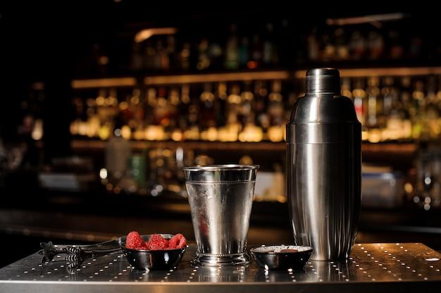 Equipamento profissional de bar, agitador, copo e tenaz dispostos no balcão do bar